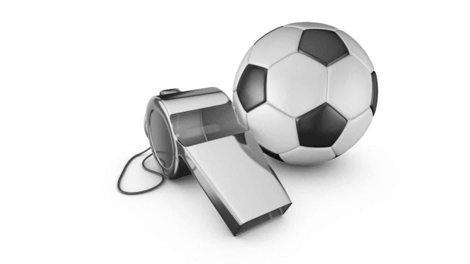 Un silbato junto a un balón de fútbol