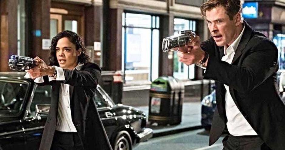 Los protagonistad de la película, Chris Hemsworth y Tessa Thompson, apuntando con sus pistolas fuera de la pantalla.