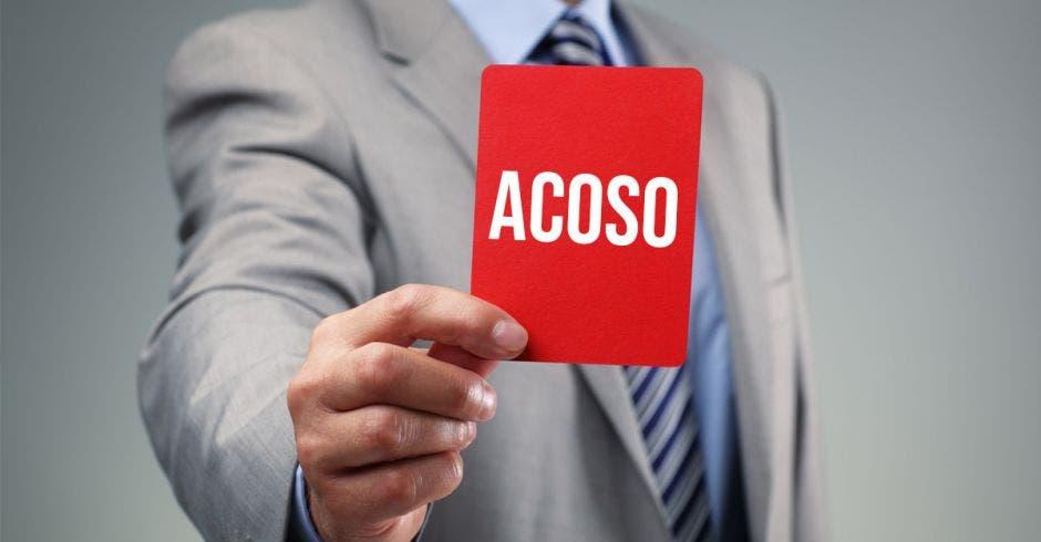 Un hombre saca una tarjeta roja que dice acoso