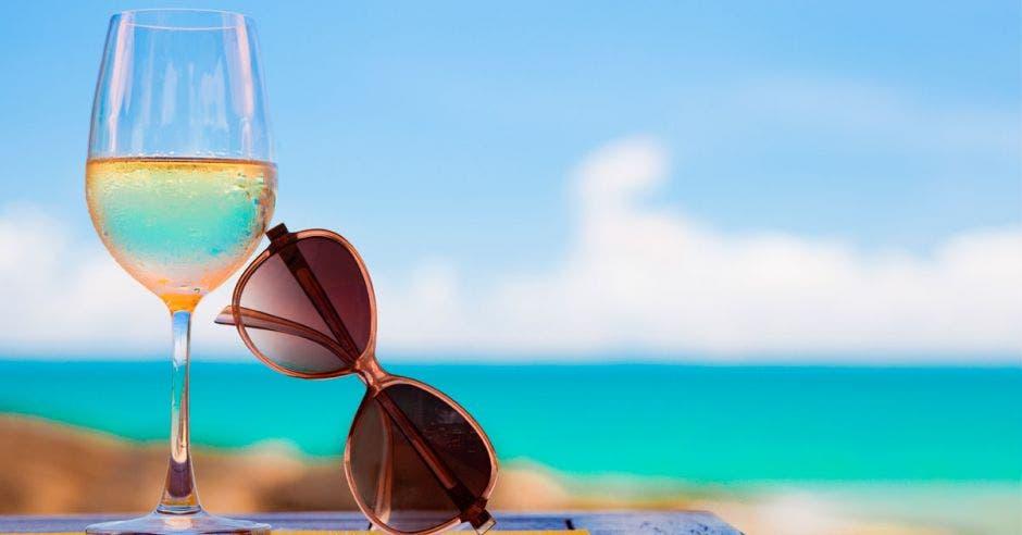 Una copa junto a unos lentes con una playa de fondo