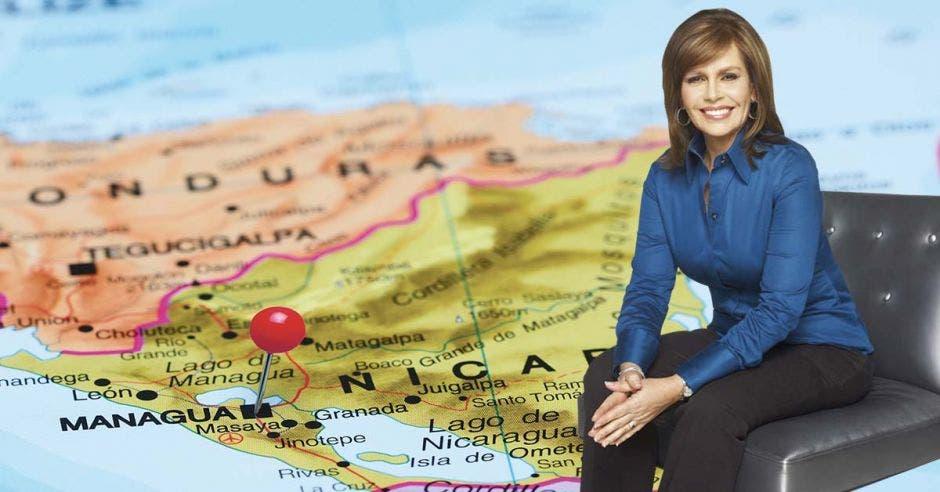Glenda Umañana sentada sobre una silla con el mapa de Nicaragua de fondo