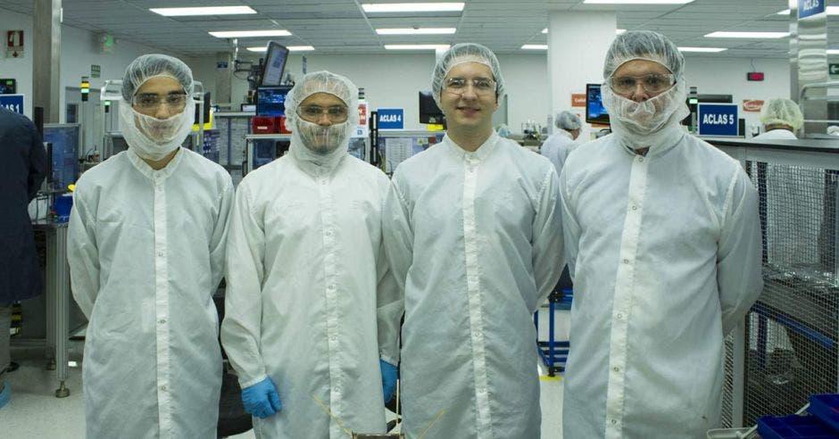 Cuatro científicos en bata junto al satélite proyecto irazú