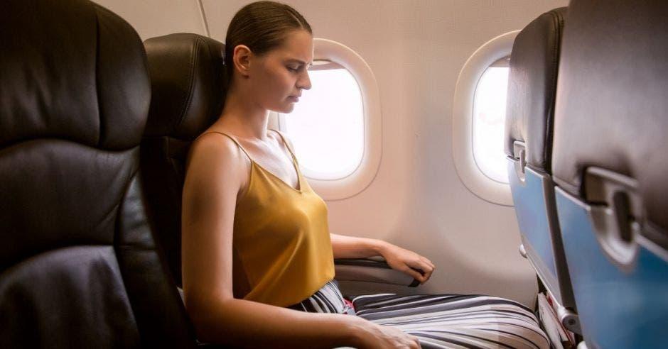 mujer sentada en un asiento de avión