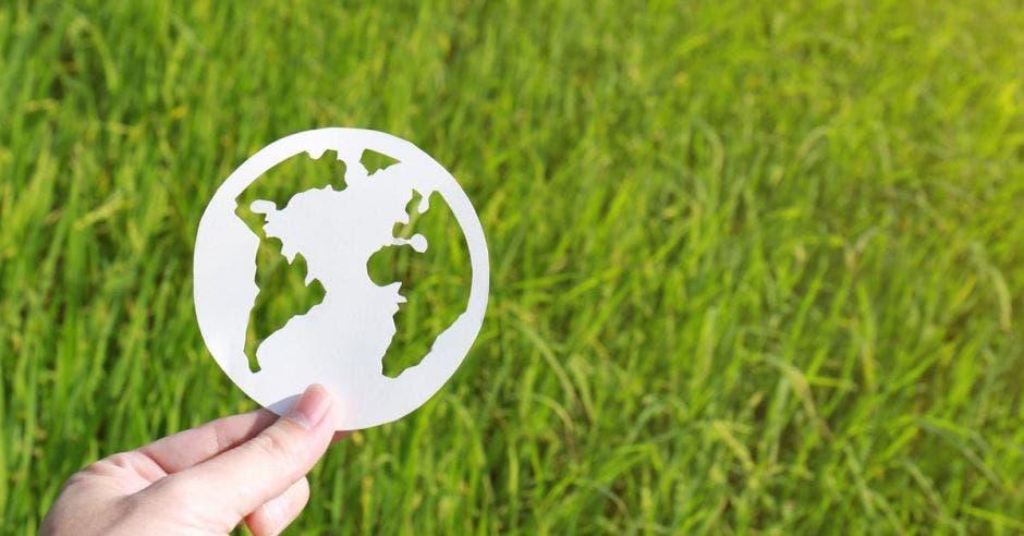Un planeta de papel sostenido sobre un fondo verde