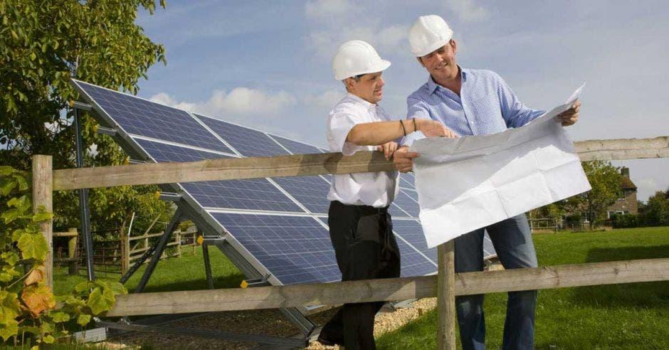 Un par de trabajadores instalan un panel solar