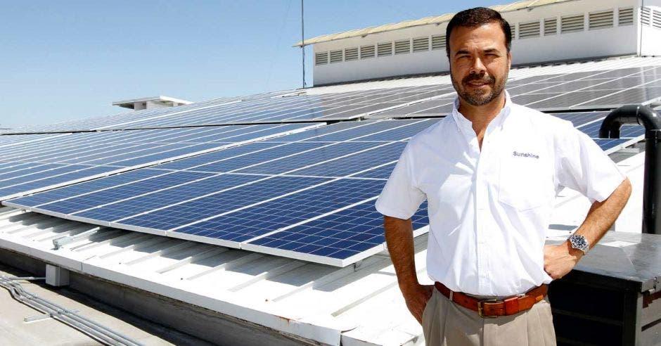 Eduardo Kopper posa en un techo con paneles solares instalados