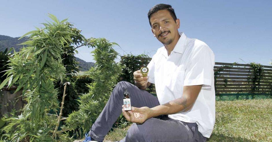 Juan Zuniga posa junto a una planta de marihuana