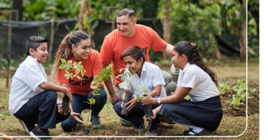 niños y adultos sembrando árboles