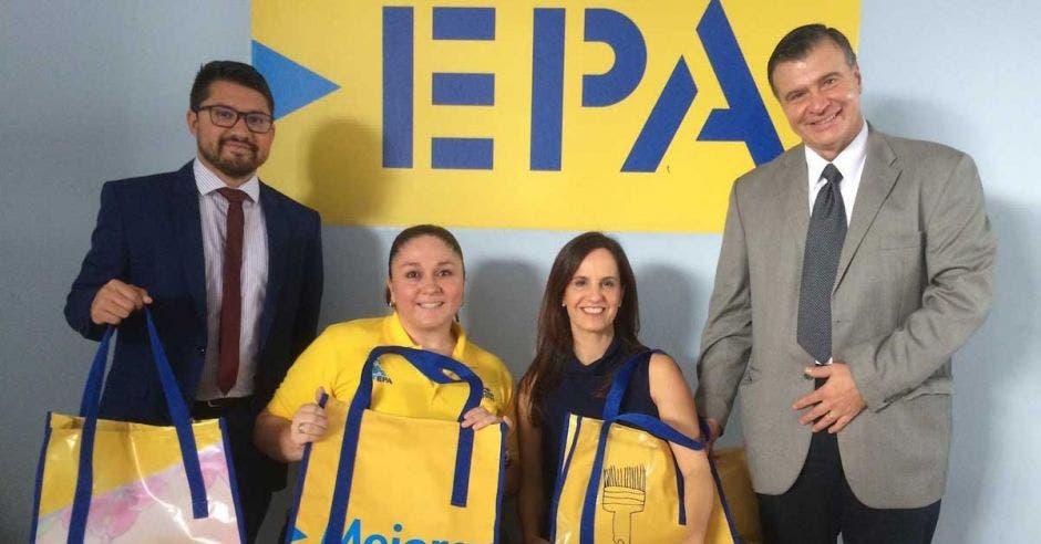 Cuatro personas frente al logo de EPA sostienen bolsas amarillas