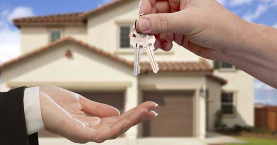 una persona entregándole unas llaves a otra, de fondo