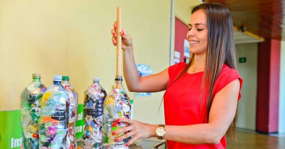 mujer echando plástico en una botella