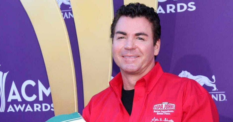 John Schnatter, de Papa John's, sostiene una pizza