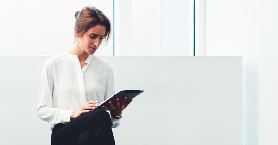 Una mujer revisa información en su tablet