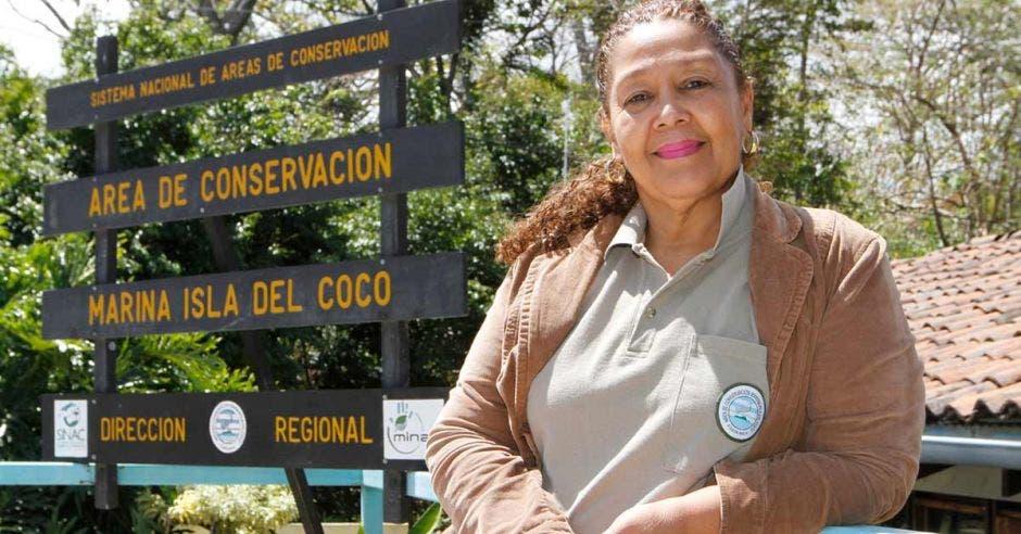 Una mujer posa junto a un letrero de parque nacional