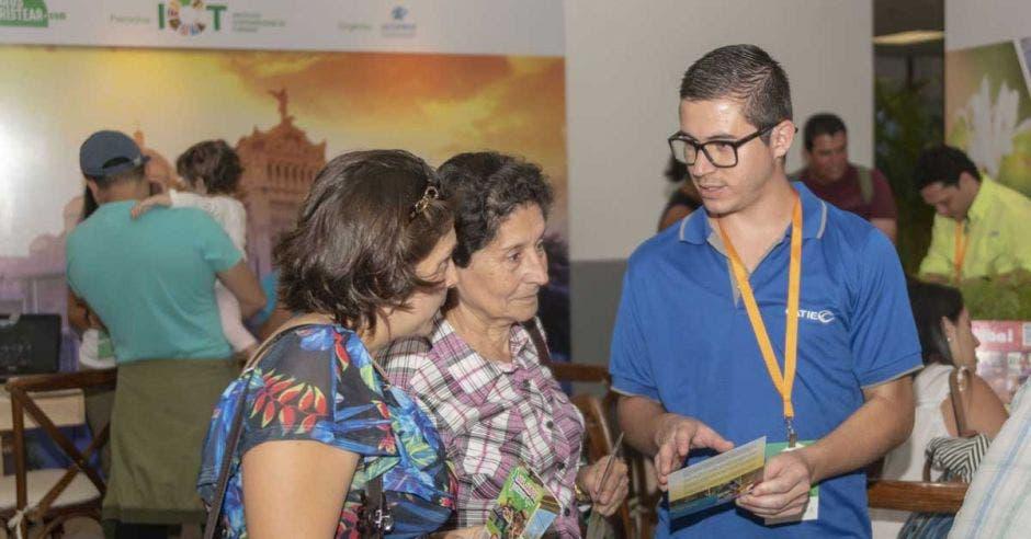 muchacho hablando con dos señoras en Expotur edición 2017