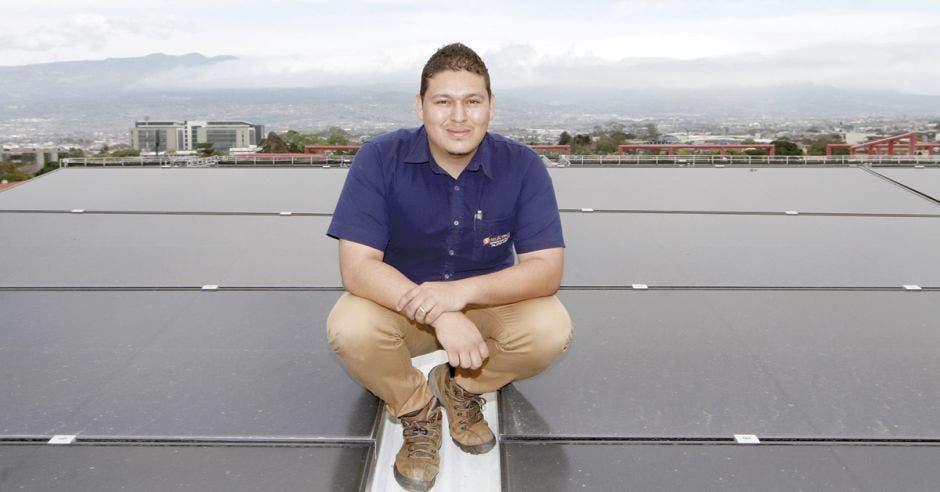 Luis Carlos Salas posa en el techo del TSE junto a los paneles solares