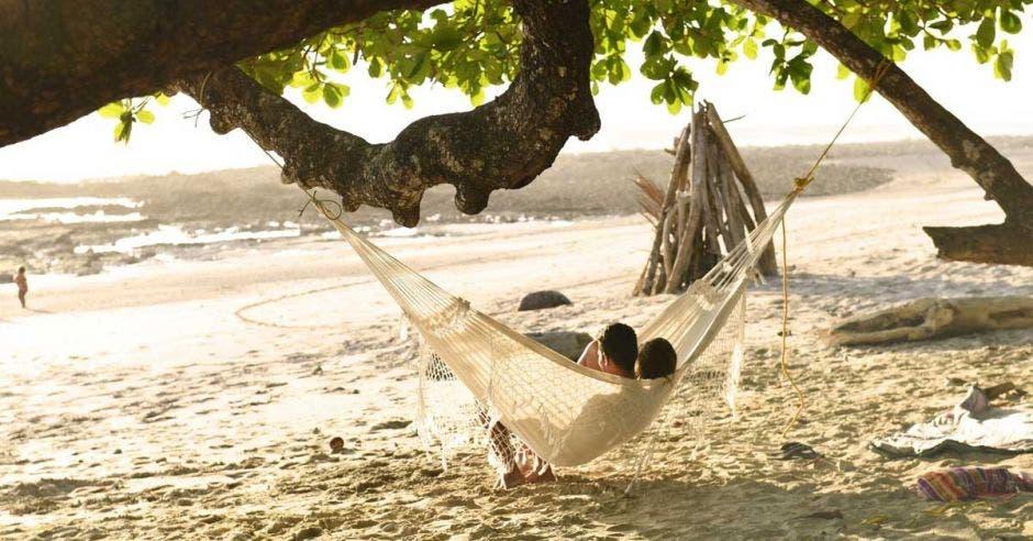 personas en una hamaca en la playa