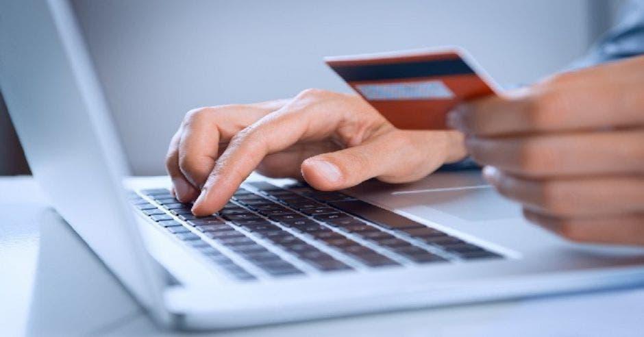 Persona con tarjeta y computadora