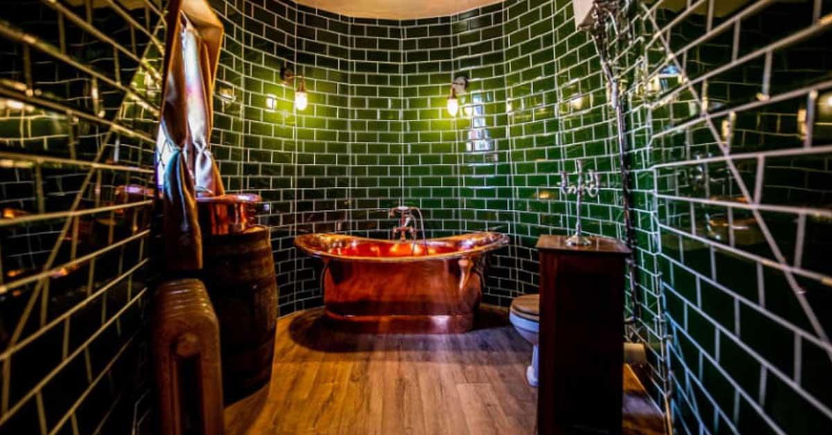 tina de baño en colo bronce, paredes verdes