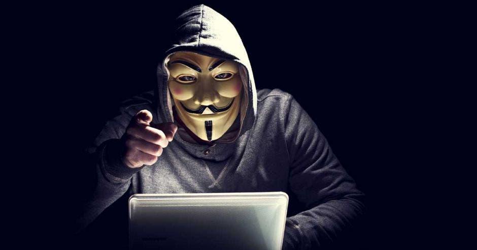 Un hombre con la máscara de Anonymus perturba a un espectador