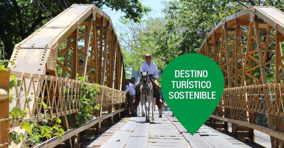 personas a caballo cruzando un puente