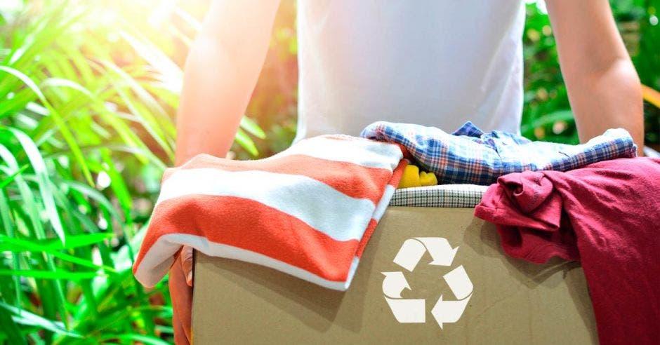 caja con logo de reciclaje, llena de ropa