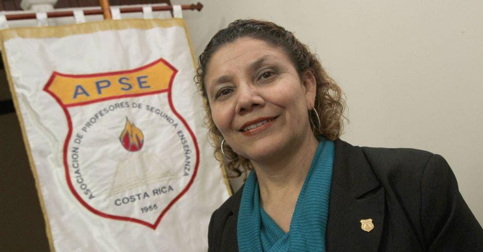 Mélida Cedeño posa para la cámara, al fondo se ve una bandera de la organización APSE.