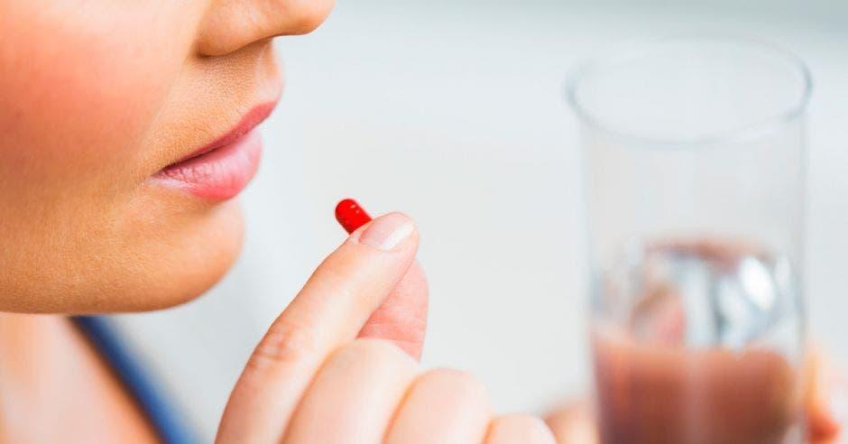 Una mujer tomando una pastilla sin que se le vea el rostro