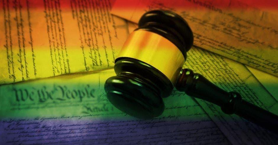 Un mazo de la justicia y de fondo varios documentos legales con los colores de la comunidad LGTB