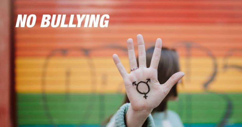 Joven con una mano frenando bullying