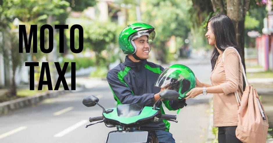Un hombre le da un casco a una mujer para que se suba a la moto.