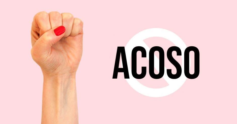 Foto de una mano femenina con el puño cerrado. Un fondo rosa y la palabra acoso con un sello de prohibido encima