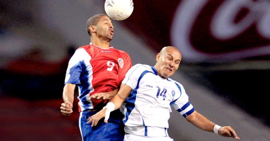 Dos jugadores de futból brincando por el balón. Alvaro Saborío por Costa Rica y Dennis Alas del Salvador