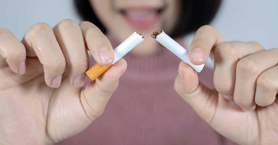 persona rompiendo un cigarro