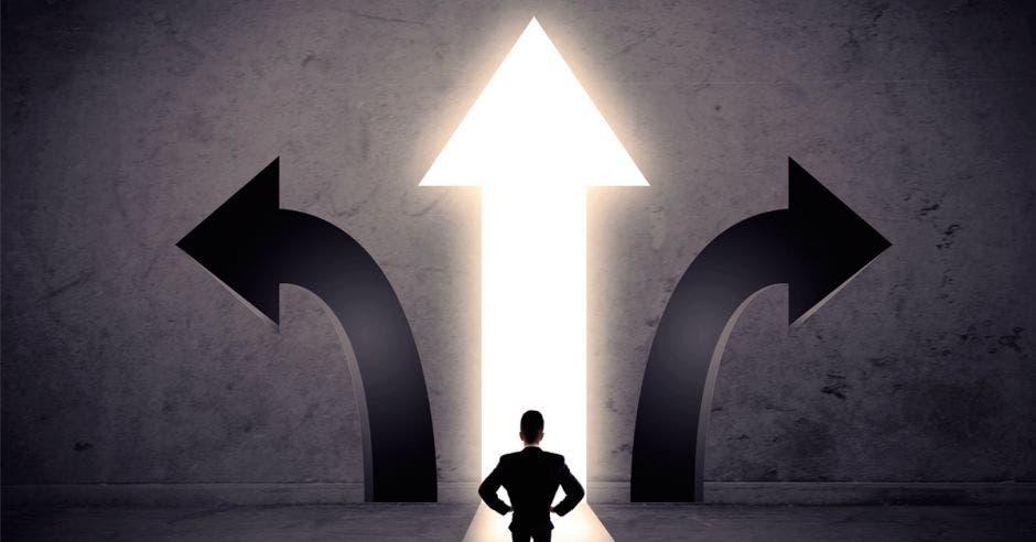 Foto de una persona decidiendo entre tres caminos