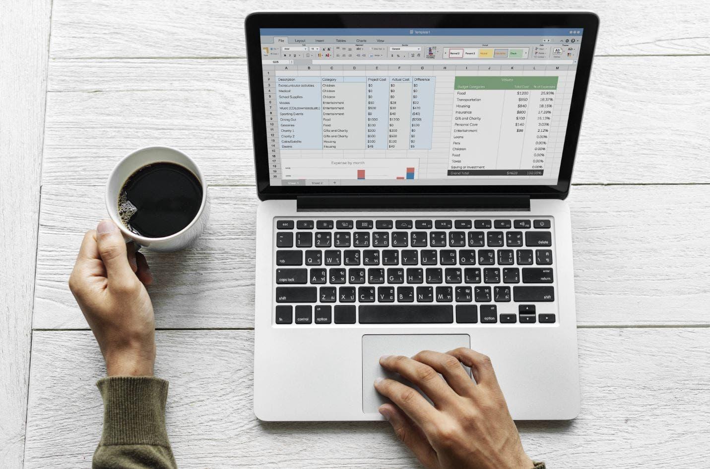 Foto de una persona usando una computadora y tomando café