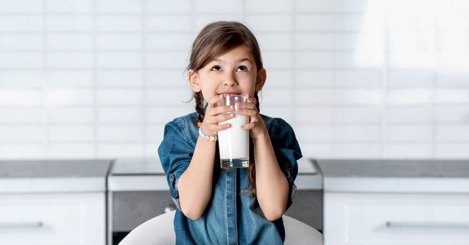 niña con un vaso de leche en las manos