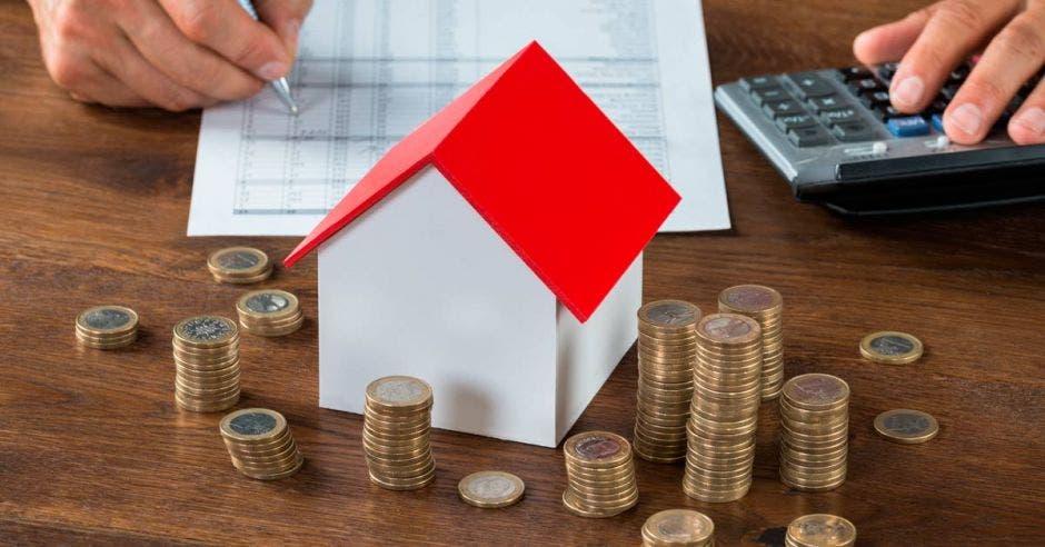 Foto de una casa pequeña sobre una mesa y a su alrededor monedas apiladas