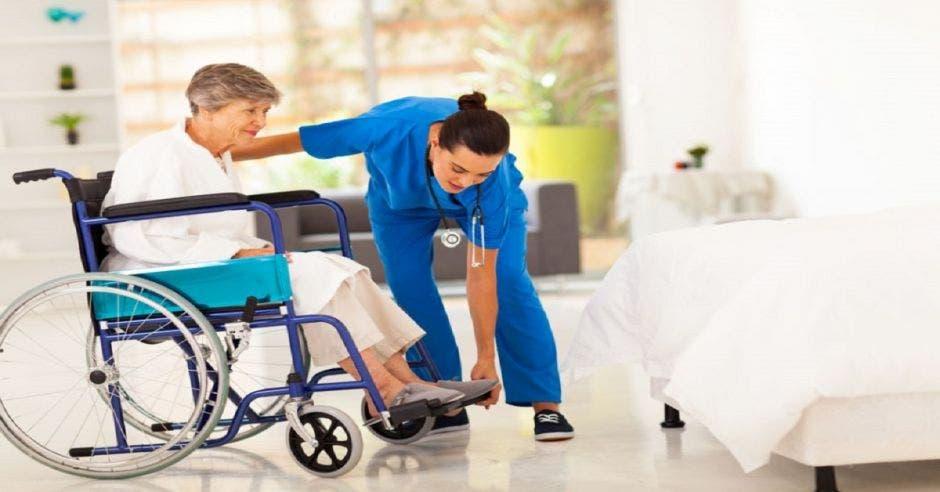 Anciana recibiendo ayuda de una enfermera