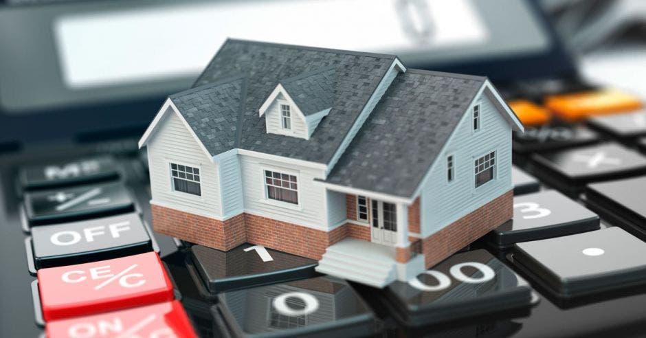 Foto de una casa miniatura sobre una calculadora