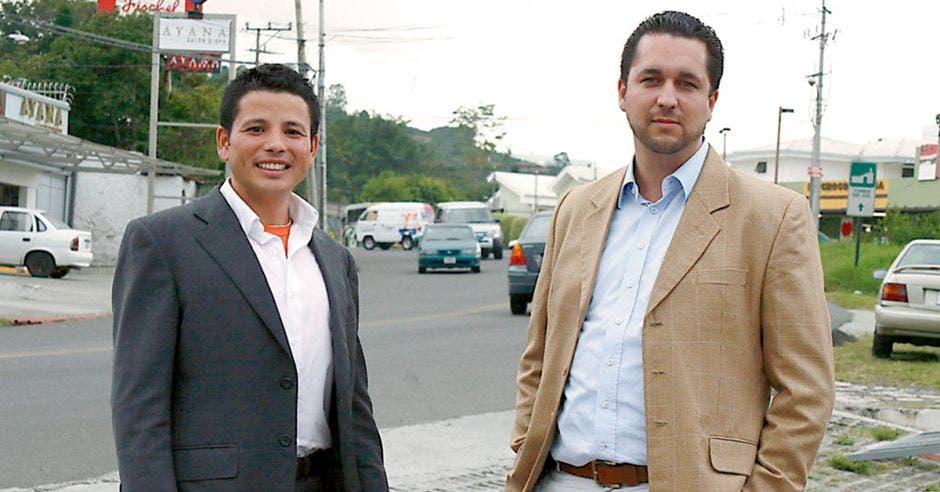 Dos hombres, ambos con traje entero ubicados en la acera
