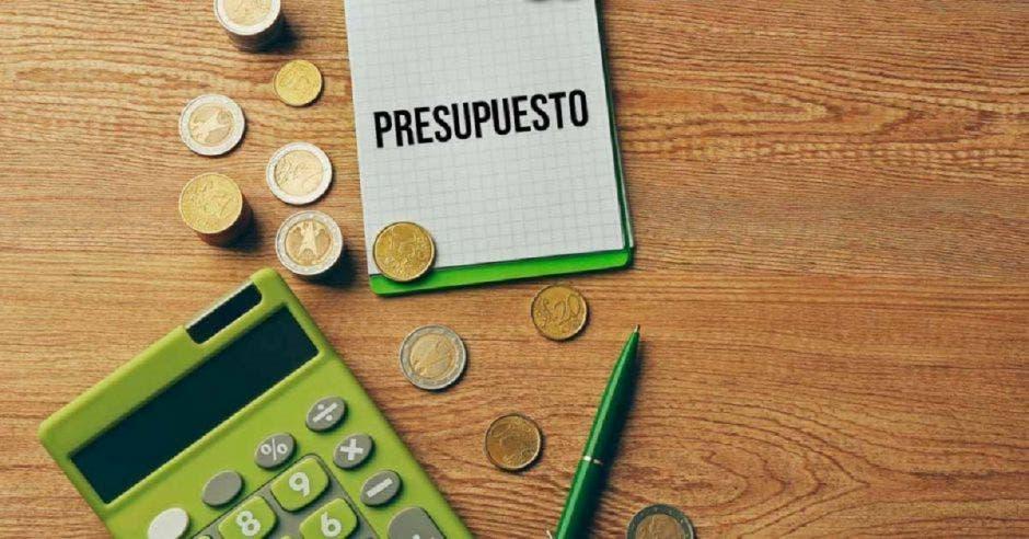 Una calculadora y unas monedas con un papel que dice Presupuesto