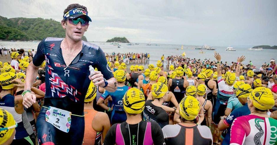 Triatlonista corre, grupo se prepara para nadar