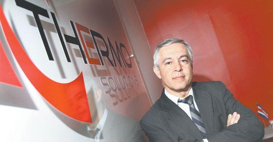Hombre con los brazos cruzados con el logo de la empresa a un costado