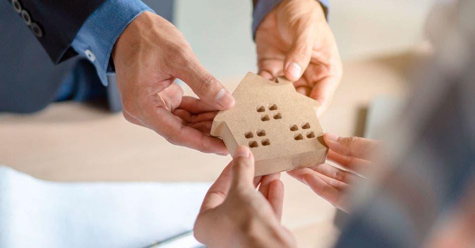 persona entregando una casita de madera a otra