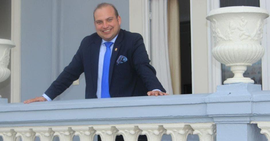 Pablo Heriberto con los brazos abiertos arrecostadoa una varanda