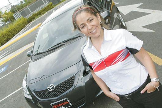 Empleada de la empresa Toyota frente a un carro de la misma empresa