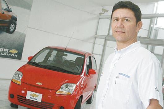 Hombre posa frente a vehículo color rojo
