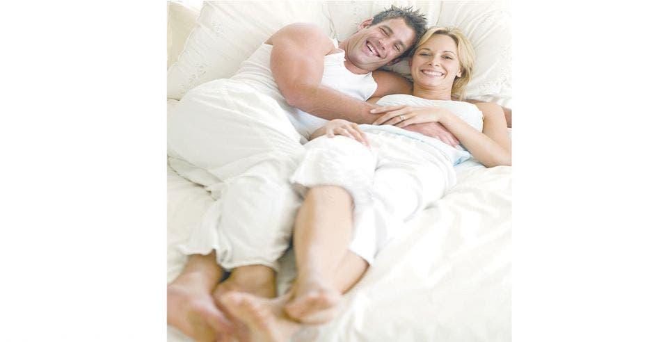 pareja hombre-mujer abrazada acostada en una cama