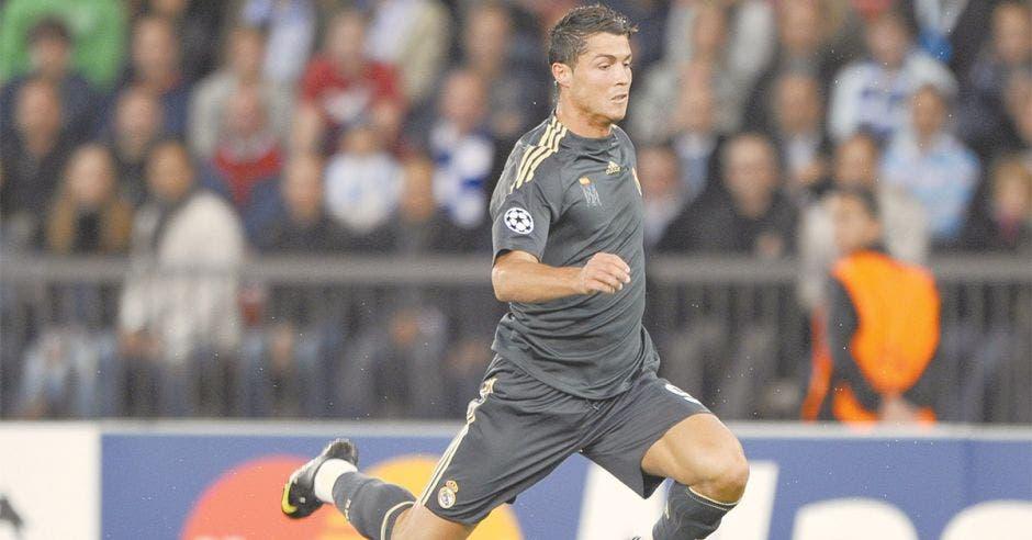 Jugador de futbol corriendo por la cancha con uniforme gris